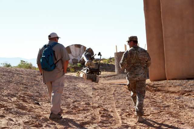 Sgt. 1st. Class Kyle R. Kinard, U.S. Army Training and Doctrine Command, capabilities manager for explosive ordnance disposal, walks with a project site manager as they assess the capabilities of the Andros FX before the Army War Fighting Assessment (AWA) 17.1 on Oct. 14 at Fort Bliss, Texas. AWA allows industry engineers to work side-by-side with Soldiers to rapidly correct and improve capabilities. (U.S. Army photo by Staff Sgt. Cashmere Jefferson, 7th Mobile Public Affairs Detachment)