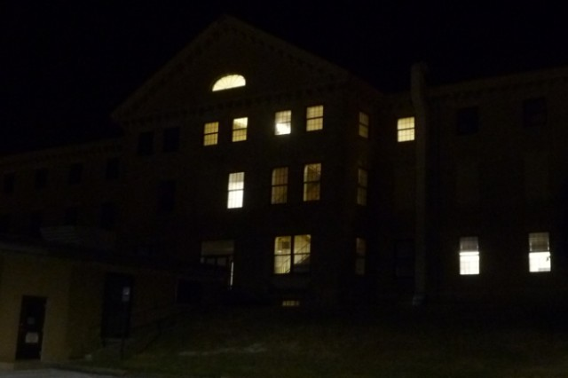 A photo of the exterior of Bldg. 131 on Rock Island Arsenal the night of the night-light survey. Only a handful of lights can be seen illuminated on the inside of the facility.