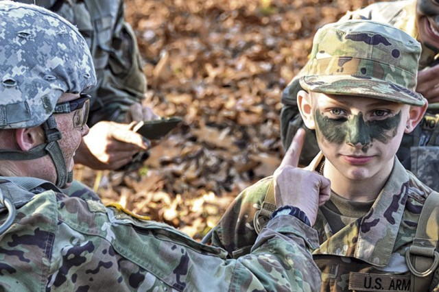 Michael Kelsey, of Marshfield, Mo., gets his camo paint applied by Pvt. Ashley Bailey, Company C, 3rd Battalion, 10th Infantry Regiment, before taking part in a training event on Fort Leonard Wood. Kelsey was named an honorary Soldier Sunday and spent the day marching, eating, training and hanging out with Soldiers in Company C. The highlight of his day was getting to ride in a Stryker, he said.