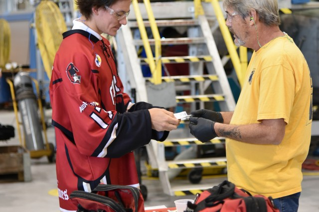 A player with the Corpus Christi IceRays gives a Corpus Christi Army Depot employee a free ticket to the team's game against the Lone Star Brahmas on Stars & Stripes Night.