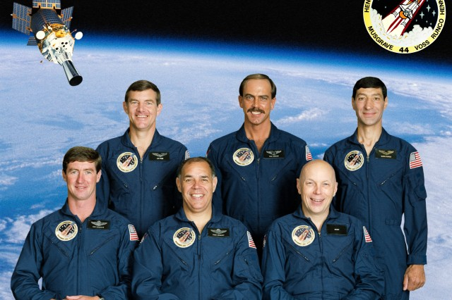 "In November 1991, Lt. Col. James Voss and Chief Warrant Officer 3 Thomas Hennen were two members of a six person crew of STS-44 and began a seven day mission aboard the Space Shuttle Atlantis, marking the first time that two Army personnel had flown aboard the same shuttle flight. STS-44 also marks another significant first as Hennen was the first and remains the only warrant officer to fly in space. Voss and Hennen are on the back row (left and center) of this STS-44 group portrait. Recognizing the Army first with this mission, the wakeup call on Nov. 26 was Irving Berlin's ""This is the Army Mr. Jones"" preceded by ""Reveille."""