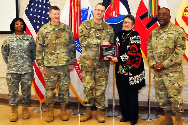 Retired Army Maj. Jo Ann Schedler receives an appreciation plaque from Col. Shawn Klawunder, First U.S. Army chief of staff, for her participation in the Rock Island Arsenal, Illinois, National American Indian Heritage Month observance Nov. 21 in Heritage Hall. Flanking them is local leadership -- Col. Lance Koenig (left), chief of staff, U.S. Army Sustainment Command; Brig. Gen. Richard Dix, commanding general, Joint Munitions and Lethality Life Cycle Management Command and Joint Munitions Command; and Command Sgt. Maj. Myris Dixon (far left), U.S. Army Garrison -- RIA. (Photo by Jon Micheal Connor, ASC Public Affairs)