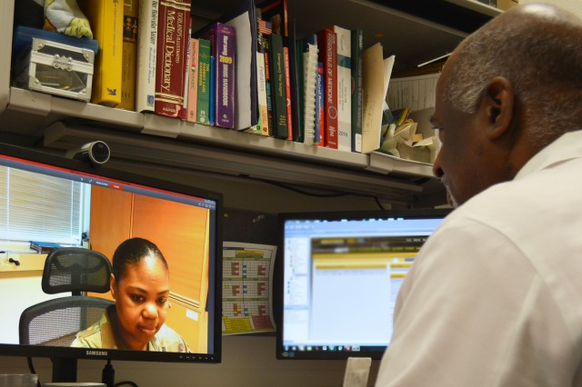 James White, Virtual Health Physician Assistant conducts a Periodic Health Assessment with Sgt. First Class LaQuanda Harrison. White uses the Virtual Integrated Readiness and Remote (VIPERR) care clinic to conduct visits with Soldiers stationed in remote parts of the world.
