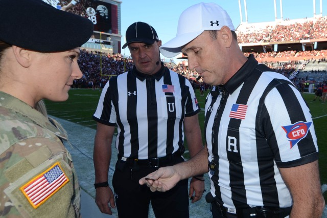 Sgt. Amanda Reuter, Fort Jackson's Soldier of the Year, listens as South Eastern Conference referees discuss how she should do the coin toss prior to the 2016 Military Appreciation Day game at Williams-Brice Stadium, Nov. 19