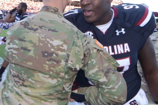 Gamecocks' defensive lineman Kobe Smith, greets Capt. Christopher Porter, aide-de-camp to the Fort Jackson commander before the team's Military Appreciation Day game against Western Carolina University Nov. 19. Fort Jackson, and Service members were honored by the University of South Carolina in pre-game and halftime festivities. The Gamecocks visited Fort Jackson before the season started and learned what it was like to face drill sergeants for the first time.