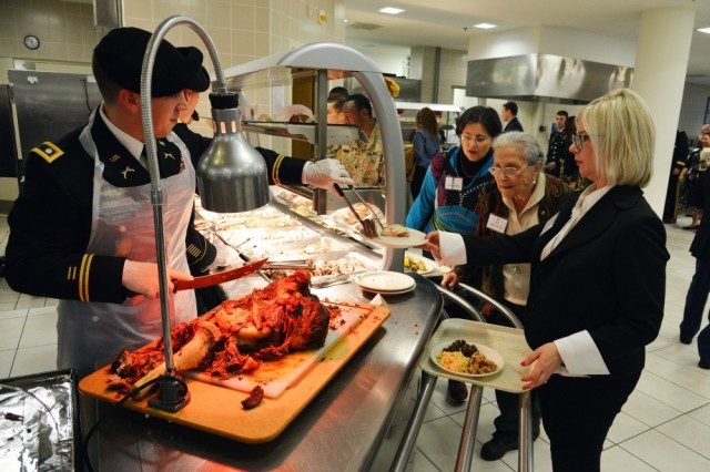 U.S. Army Lt. Col. Matthew Jemmott, assigned to U.S. Army Africa, serves lunch to Prof. Paola Del Din during the Thanksgiving lunch celebration at Caserma Del Din in Vicenza, Italy Nov. 22, 2016.