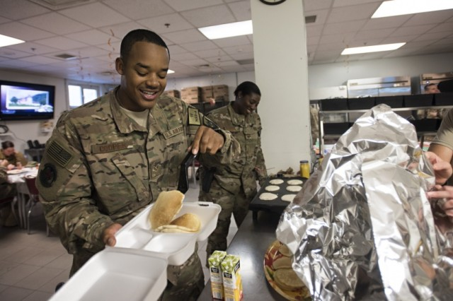Senior Master Sgt. Amy Riley, 455th Expeditionary Medical Operations Squadron superintendent, offers homemade pancakes to Senior Airman Ramod Cooper, 455th Expeditionary Medical Operations Squadron logistics specialist, on Thanksgiving, Nov. 24, 2016 at Bagram Airfield, Afghanistan. Service members around Bagram celebrated the holiday away from home with games, food and camaraderie.
