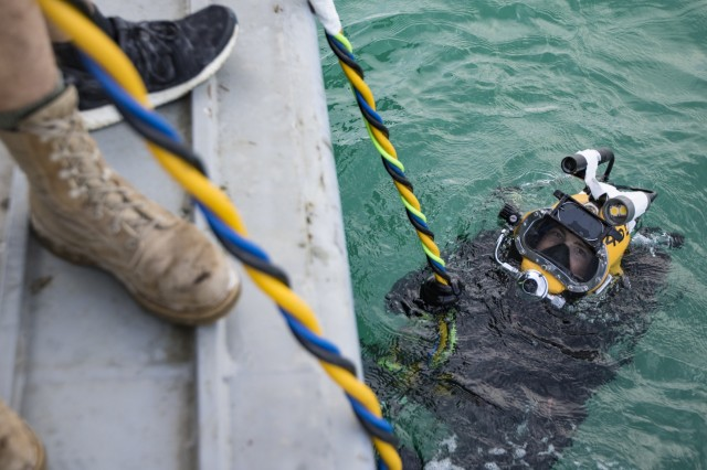 Soldiers with the 511th Engineer Dive Detachment from Fort Eustis, Va., help U.S. Army engineer divers don their equipment for diver training, Nov. 18, 2016, while aboard the MG Charles P. Gross (Logistics Support Vessel-5) off the coast of Kuwait Naval Base. The unit executed various diving techniques and certified diving supervisors in emergency protocol throughout the exercise, Operation Deep Blue, enhancing the team's overall readiness and ability to support U.S. Army Central missions.