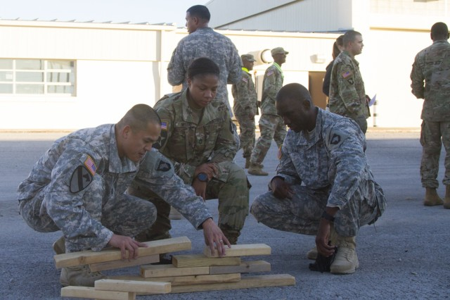(Left to right) Capt. Kenny K. Nguyen, Sgt. 1st Class Lashelle Webb, and Capt. Abdoul R. Kane, all with 101st Airborne Division (Air Assault) Sustainment Brigade, 101st Abn. Div., work together to properly place the blocks in the correct position, Nov. 9, 2016, with the help of their fourth team member, Maj. Jose G. Beltre (behind the group), who has an image of how the assembled pieces should look during the Command Team Physical Training Challenge at the 74th Composite Transportation Company motor pool on Fort Campbell, Ky. (U.S. Army photo by Sgt. Neysa Canfield/101st Airborne Division Sustainment Brigade Public Affairs)