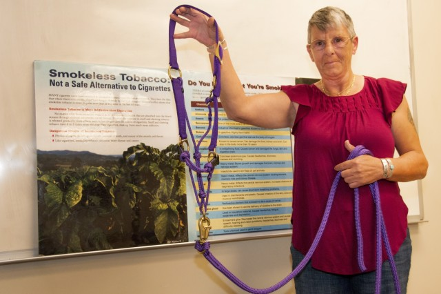 Ann Yates, 61-year-old military spouse and former smoker, holds up the harness for a horse she plans to purchase with money saved after quitting a 50-year-old habit of smoking cigarettes after a class with the Tobacco Cessation Program offered by Health Promotion and Wellness Center, Spc. Hugo V. Mendoza Soldier Family Care Center, William Beaumont Army Medical Center, Nov. 15. Yates, a native of Accrington, Lancashire County, England, attends the Tobacco Cessation classes to find support and help others who are struggling to quit using tobacco products.