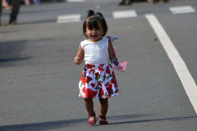 A little flag-waving girl chases after the marching platoon from the 2nd Battalion, 27th Infantry Regiment, 3rd Brigade Combat Team, 25th Infantry Division, during the 70th Annual Wahiawa Veterans Day parade at Wahiawa, Hawaii, on Nov. 11, 2016. Her mother caught her before she followed the Soldiers to Wahiawa District Park. (U.S. Army photo by Staff Sgt. Armando R. Limon, 3rd Brigade Combat Team, 25th Infantry Division)