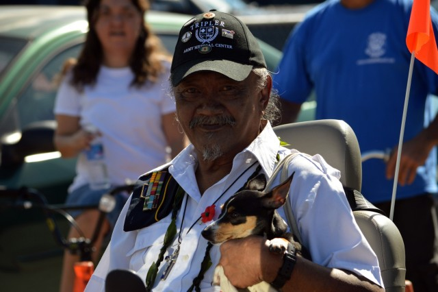 A U.S. Army and Vietnam War veteran smiles as he holds his dog as he watches the 70th Annual Wahiawa Veterans Day parade at Wahiawa, Hawaii, on Nov. 11, 2016. The Wahiawa parade is the oldest Veterans Day parade in the state of Hawaii. (U.S. Army photo by Staff Sgt. Armando R. Limon, 3rd Brigade Combat Team, 25th Infantry Division)