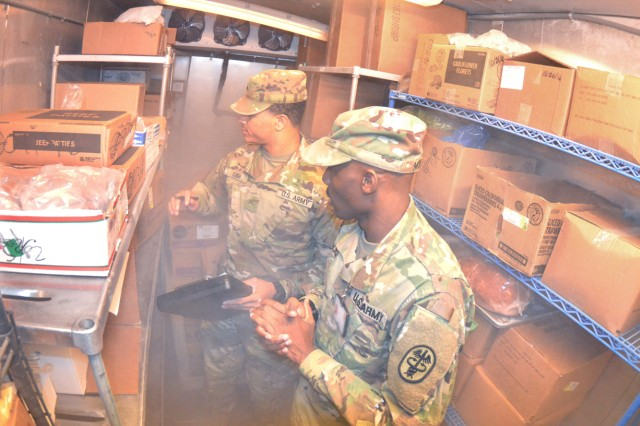 Pvt. Kintavious Cash and Pfc. Markell McKee of the installation Veterinary Services check food items in freezer  during an inspection of a food training facility recently.  Cash, a 19-year-old native of Morehouse Parrish, La., and McKee a 22-year-old from Savannah, Ga.,  inspect food and storage areas and check expiration dates on packaging among performing other tasks on a weekly basis.