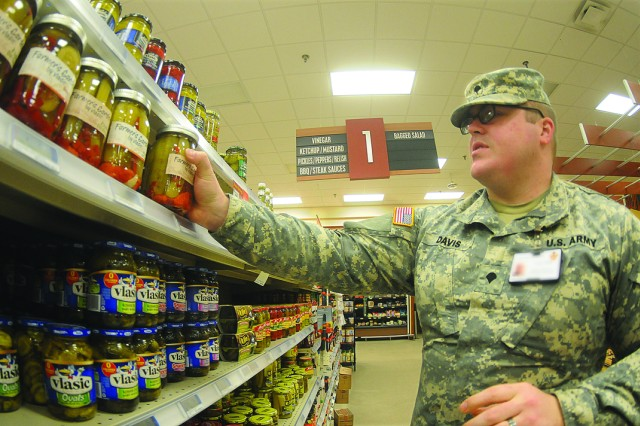 Spc. Tyler Davis, Fort Lee Veterinary Services, looks for the expiration dates of food products at the Defense Commissary Agency store here recently.  Davis, a veterinary food inspection specialist, is part of the effort that ensures food safety and security on installations all over the world.