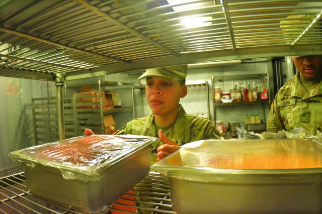 Spc. Tatiana Ortiz, a 25-year-old Veterinary Services food inspection specialist from Puerto Rico, takes a whiff of and look at stored food products shelved at a Fort Lee culinary training facility recently.