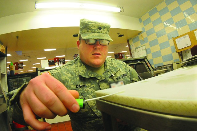 Spc. Tyler Davis, Fort Lee Veterinary Services, uses a swab to test a food preparation area for bacteria at the Defense Commissary Agency store here recently.  Davis, a veterinary food inspection specialist, is part of the effort that ensures food safety and security on installations all over the world.