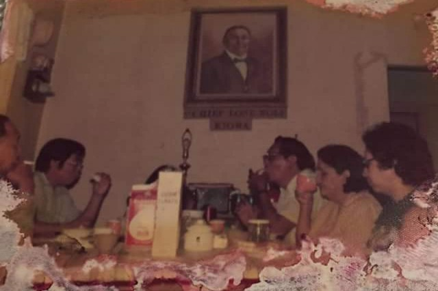 This old family photo shows Denise Wickson's family gathered at a table below an image of their ancestor, Kiowa Chief Lone Wolf the Younger. Wickson is a U.S. Army Corps of Engineers, Southwestern Division civil servant who is sharing her family story in observance of Native American Indian Heritage Month.