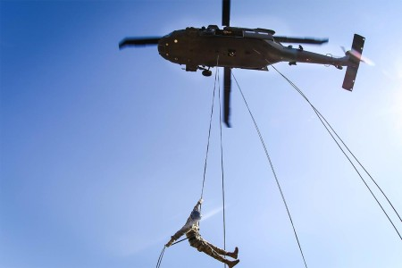 An instructor from the DeGlooper Air Assault School, XVIII Airborne Corps, demonstrates the safe and proper way to rappel from an UH-60 Black Hawk assigned to 2nd Assault Helicopter Battalion, 82nd Combat Aviation Brigade, 82nd Airborne Division at Fort Bragg, N.C., Nov. 17.