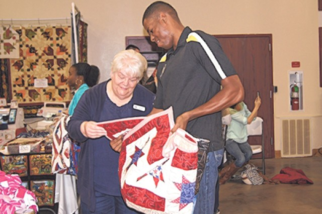 "Sgt. Paville Simpson, Company D, 2-10th Infantry Battalion, and Fort Leonard Wood's BOSS president, admires the ""Eagle Panel"" quilt with quilt-maker Mary Jensen."