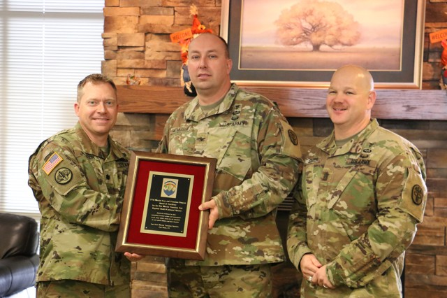 Col. John McMurray, center, U.S. Army Medical Department Activity - Fort Drum commander, and Command Sgt. Maj. Brian Stauffer, right, Fort Drum MEDDAC senior enlisted adviser, present Lt. Col. Brad Johnson, 3-85th Warrior Transition Battalion commander, with the Best Warrior Transition Unit in the Regional Health Command (Atlantic).
