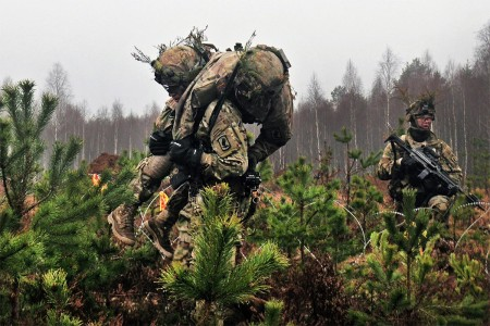 "A Paratrooper carries a ""wounded"" comrade off the battlefield, Nov. 24, during Exercise Iron Sword 2016, in Pabrade, Lithuania. The Soldier is from Able Company, 2nd Battalion, 503rd Infantry Regiment, 173rd Infantry Brigade Combat (Airborne). Iron Sword is an international training exercise featuring 11 NATO countries and about 4,000 troops. The exercise is designed to test promote regional stability and security, while strengthening partnership capacity, and fostering trust while improving the ability to conduct joint training between Lithuania, the U.S., and NATO member nations."