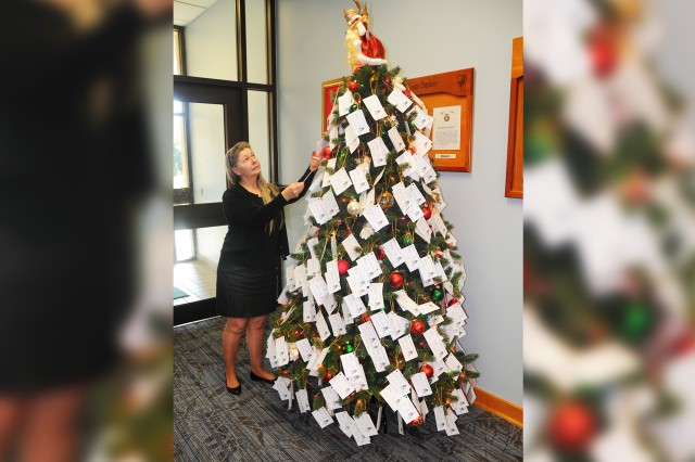 Therese Erthal, Catholic parish coordinator, puts tags on the angel tree in the main post chapel in 2012.
