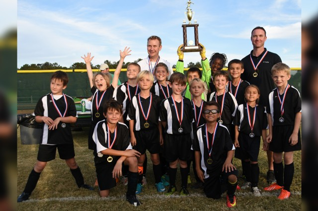 The Fort Rucker Youth Sports all-star 9-and-under soccer team, Black Hawks, celebrate with their trophy after winning the district championship tournament in Dothan Nov. 5.