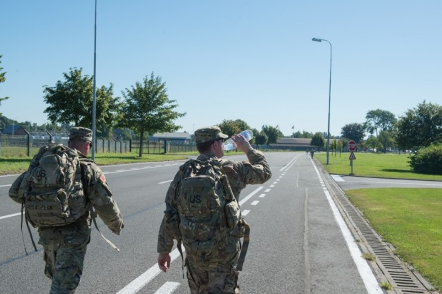 U.S. Army Sgt. 1st Class Gerardo Lopez, and Capt. Sean Raleigh, who hydrates himself, with Headquarters and Headquarters Company, Allied Forces North Battalion, U.S. Army NATO Brigade, perform their monthly ruck march, on Chièvres Air Base, Belgium, Aug. 25.