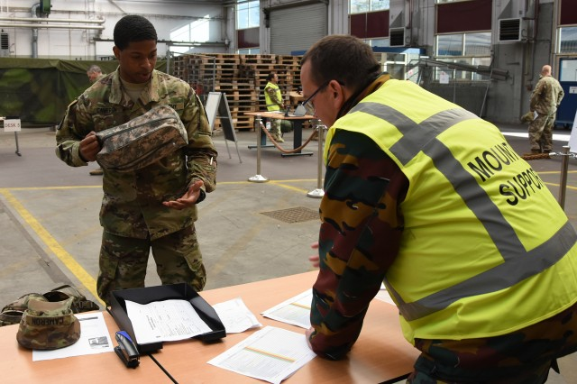BRUNSSUM, Netherlands -- A Soldier assigned to the NATO Joint Force Command, Brunssum shows items from his personal issue to a multinational support Soldier during the recent JFC Brunssum readiness drill. (photo by Greg Jones, U.S. Army NATO Brigade)