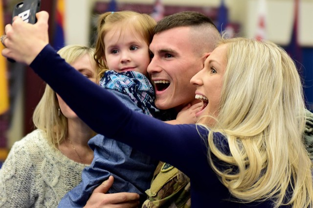 Sgt. Matthew Brock of the 109th Transportation Company poses for a family reunion selfie, Dec. 1, at Joint Base Elmendorf-Richardson's Buckner Physical Fitness Center. The 109th, part of U.S. Army Alaska's 17th Combat Sustainment Support Battalion, deployed to Kuwait in March in support of Operation Inherent Resolve.