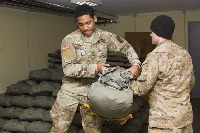 """U.S. Army Pfc. Estefan Daza, native of Miami, Fla., 19-year-old parachute rigger, assigned to 601st Quartermaster Company, Brigade Support Battalion, 173rd Airborne Bridade, passes a parachute to a Paratrooper assigned to 2nd Battalion, 503rd Infantry Regiment, 173rd Airborne to load onto a truck for an upcoming airborne operation, Dec. 2, 2016 at Camp Adazi, Latvia. The """"Sky Soldiers"""" of 2nd Bn., 503rd Inf. Regt., are on a training rotation in support of Operation Atlantic Resolve, a U.S. led effort in Eastern Europe that demonstrates U.S. commitment to the collective security of NATO and dedication to enduring peace and stability in the region. The 173rd Airborne Brigade, based in Vicenza, Italy, is the Army Contingency Response Force in Europe, and is capable of projecting forces to conduct a full range of military operations across the United States European, Central and Africa Command areas of responsibility within 18 hours. (U.S. Army Photo by Pfc. James Dutkavich/Released)"""