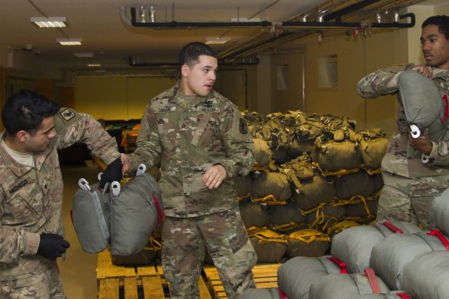 """U.S. Army parachute riggers assigned to 601st Quartermaster Company, Brigade Support Battalion, 173rd Airborne Brigade, pass parachutes to U.S. Army Paratroopers assigned to 2nd Battalion, 503rd Infantry Regiment, 173rd Airborne to load onto a truck for an upcoming airborne operation, Dec. 2, 2016 at Camp Adazi, Latvia. The """"Sky Soldiers"""" of 2nd Bn., 503rd Inf. Regt., are on a training rotation in support of Operation Atlantic Resolve, a U.S. led effort in Eastern Europe that demonstrates U.S. commitment to the collective security of NATO and dedication to enduring peace and stability in the region. The 173rd Airborne Brigade, based in Vicenza, Italy, is the Army Contingency Response Force in Europe, and is capable of projecting forces to conduct a full range of military operations across the United States European, Central and Africa Command areas of responsibility within 18 hours."""