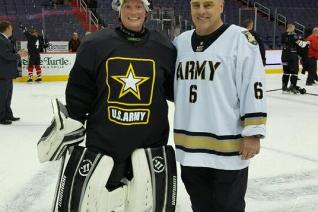 Army hockey coach and also Army Chief of Staff Gen. Mark A. Milley poses for a winning photo after the game against Navy with most valuable player goaltender Air Force Capt. Lindsey Colburn at the Verizon Center in Washington, D.C., Dec. 5, 2016.