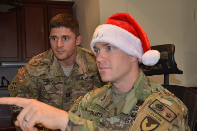 (From left) Maj. Erich Roberts, executive officer for the Office of the Program Manager, Saudi Arabian National Guard, shares information and holiday cheer Nov. 30, 2016, with Capt. Joe Davis, OPM-SANG's battalion advisor for the Prince Saad Abdulrahman Mechanized Brigade.