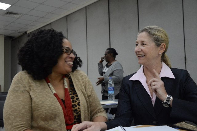 (From left) Lee Ethel Edwards, management analyst with OPM-SANG's G1, and Sarita Garrison, the Performance Management Program manager at AMC G1, discuss the DPMAP during a Dec. 5-6 New Beginnings class Garrison conducted for AMC personnel in Saudi Arabia.