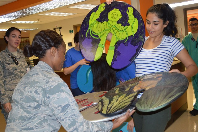 """Amaya Mali presents several IV pole """"lilypads"""" to Maj Carla Cox, pediatric clinical nurse specialist. Mali and two other students from the Westlake Robotics Club in Austin, Texas, donated 10 of the wooden pads to Brooke Army Medical Center Dec. 1, 2016. U.S. Army photo by Elaine Sanchez"""