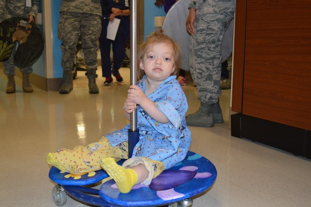 """Annabelle Johnson, the 19-month-old daughter of Air Force Tech. Sgt. Evan Johnson, enjoys riding on a new IV pole """"lilypad"""" in the pediatric ward at Brooke Army Medical Center Dec. 1, 2016."""