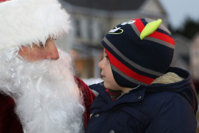 """A little boy smiles at Santa while he sits on his lap and tells him what kind of presents he would like for Christmas during a Fort Drum Mountain Community Homes """"Santa Sightings"""" event Dec. 2 on post. The Mountain Community Homes staff hosts events like this to help give military Families a """"home away from home"""" feeling while they are stationed here."""