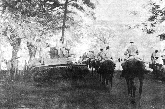 Soldiers from the 26th Cavalry Regiment (Philippine Scouts) pass a General Stuart light tank, M3, in the battle for the Philippines, December 1941. Soldiers from the regiment took part in the last mounted cavalry charge in U.S. history, Jan. 16, 1942 in a battle against the Japanese.