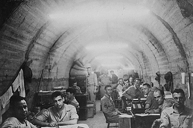 "During the siege of Corregidor, Philippines, a massive tunnel complex protected Army staff and hospital patients from constant Japanese bombardments. The finance office (foreground) and the Signal Corps shared lateral Number 12 of the Malinta Tunnel. Soldiers forced to fight in the open scathingly called them ""tunnel rats."""