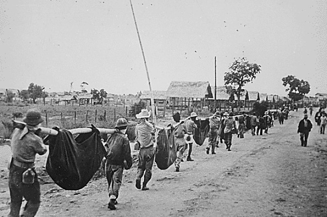 American and Filipino prisoners of war carry dead comrades in makeshift litters as part of a burial detail at Camp O'Donnell, Philippines, May 1942, after the Bataan Death March. Survivors would face almost four years in brutal captivity, enduring torture, starvation, disease and slave labor.