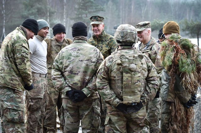 Chairman of the Joint Chiefs of Staff Marine Corps Gen. Joe Dunford engages troops with the 2nd Cavalry Regiment at a shooting range at Grafenwoehr Training Area. Gen. Dunford and his senior enlisted advisor, Army Command Sgt. Maj. John W. Troxell, headed this year's USO Holiday Tour and visited with Soldiers and families, Dec. 8, stationed at U.S. Army Garrison Bavaria headquartered in Grafenwoehr, Germany. Olympic gold medalist Maya DiRado, NBA legend Ray Allen, musician Craig Campbell and mentalist Jim Karol accompanied Dunford on the tour.