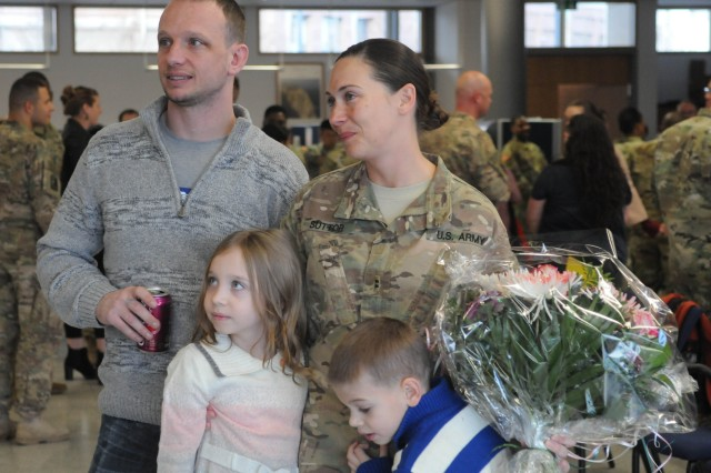 RAMSTEIN, Germany- Chief Warrant Officer Jamie Suttor stands with family after returning home from nine month deployment. Dec. 8. (Photo by Brittany Jones 21st Public Affairs)
