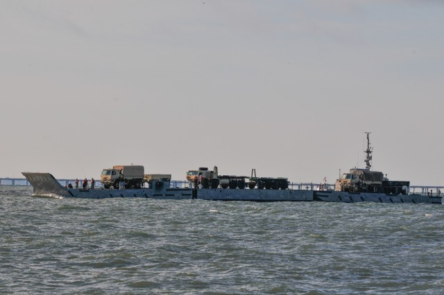Soldiers from the 7th Transportation Brigade (Expeditionary) conduct over-the-shore operations as a part of Resolute Endeavor II December 5, 2016, near the coast of Utah Beach, Fort Story, Va. The vehicles are sailing on a Modular Warping Tug from the 331st Transportation Company (Modular Causeway System), 10th Transportation Battalion (Terminal), 7th Transportation Brigade (Expeditionary). Once the boat lands on the beach, the vehicles will continue on with their mission. Resolute Endeavor II is a joint logistics over-the-shore training exercise that evaluates the 7th Transportation Brigade's (Expeditionary) readiness to conduct maneuver on the move concepts and implement the modular causeway system in preparation for the combined joint logistics over-the-shore exercise taking place in the near future in Korea.  (U.S. Army photo by Sgt. Ondirae Abdullah-Robinson/22nd Mobile Public Affairs Detachment)