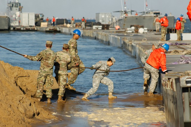 Soldiers assigned to the 331st, 10th Transportation Battalion (Terminal), 7th Transportation Brigade (Expeditionary) attach a tethering line to the floating pier December 2, 2016 near Ft. Story, Va.  Resolute Endeavor II is a joint logistics over-the-shore training exercise that evaluated the 7th Transportation Brigade's (Expeditionary) ability to deliver supplies and equipment from ships at sea to land without pre-existing ports. (U.S. Army photo by Sgt. David Anderson/7th Transportation Brigade)