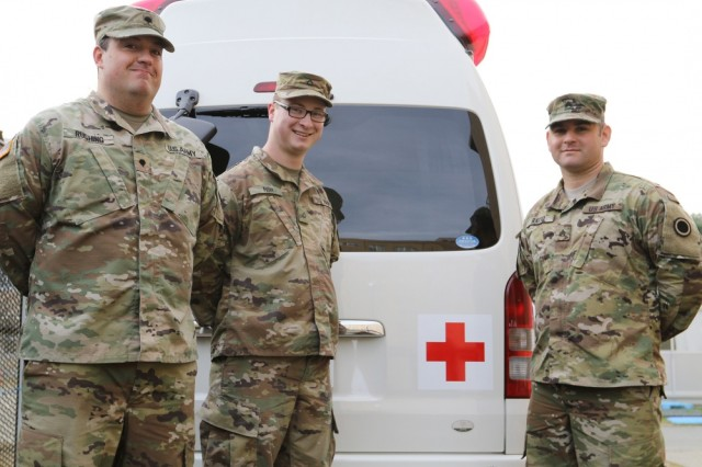I Corps Army Combat Medics Sgt. Mario Ratto, Spc. Sandy Rushing and Pfc. Jonathan Fish stand in front of a Japanese EMT vehicle on Camp Kengun, Japan, Dec. 12, 2016. The three Soldiers were first responders to a seriously injured, elderly Japanese man while they were on pass visiting the city of Kumamato, Japan, 1 Dec.