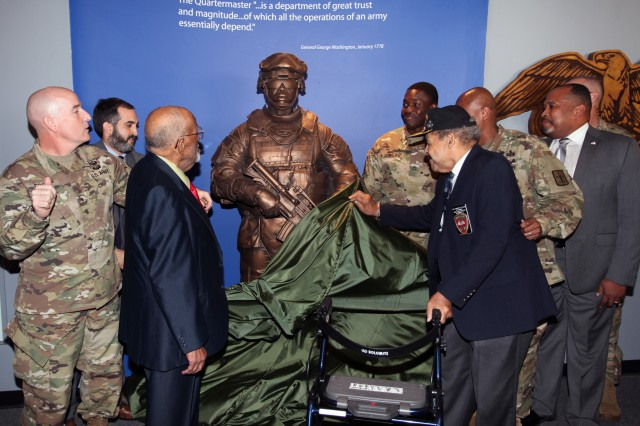 From left to right; Brig. Gen. Rodney Fogg, Quartermaster General and Quartermaster School commandant; Paul Morando, Quartermaster Museum director; retired Lt. Col. Lewis Martin, World War II veteran and Camp Lee trained Quartermaster Soldier; Staff Sgt. Sidy Diallo, logistics specialist and model for the statue; retired Col. Porcher Taylor, World War II veteran; Command Sgt. Maj. Jimmy Sellers, Quartermaster School command sergeant major and Greg Mason, Logistics Training Department director, unveiled a statue dedicated to Quartermaster Soldiers during the 75th anniversary ceremony Dec. 7 at the Quartermaster Museum on Fort Lee, Va.Diallo was the model for the statue and is one of five Soldiers who have statues created in their likeness which are displayed in the museum.