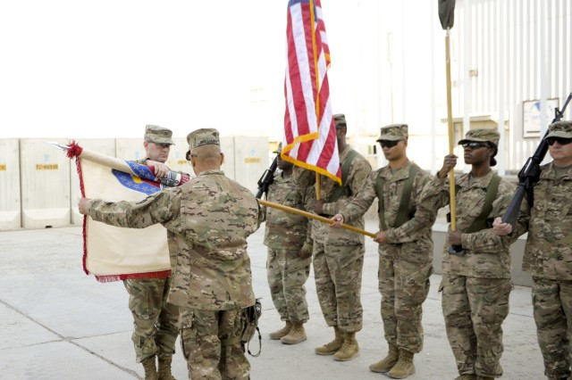 Col. Josh Burris and Command Sgt. Maj. Charles Williams uncase the 410th Contracting Support Brigade organizational colors during an Expeditionary Contracting Command-Afghanistan transfer of authority ceremony Dec. 3 at Bagram Airfield, Afghanistan. Members of the 410th CSB deployed from Joint Base San Antonio-Fort Sam Houston, Texas, in November to relieve the 419th CSB, which returns to Fort Bragg, North Carolina. Burris is the 410th CSB commander and Williams is the brigade command sergeant major.