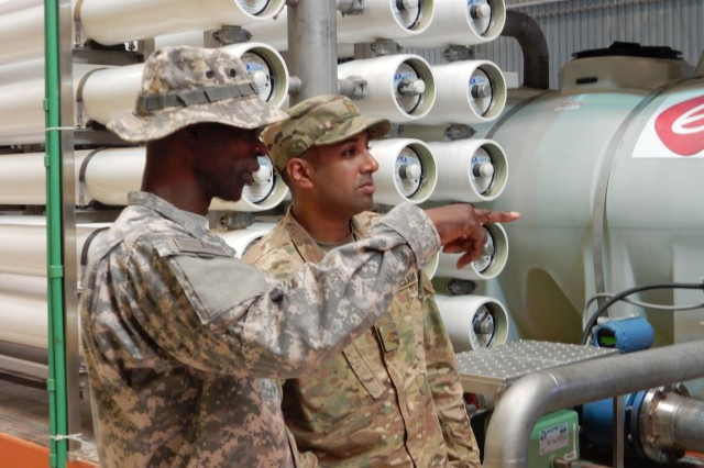 ECC-A Property Book Officer Michael L. Mangum, left, and Maj. Reuben T. Joseph, chief of the Regional Contracting Office -- South, discuss the operations of the main reverse osmosis water purification unit at Kandahar Air Field, Afghanistan. Joseph was the KAF transition coordinator for the ECC-A Regional Contracting Office -- South, ensuring that services were provided without interruption during the transition from NATO contracts to LOGCAP. (All images courtesy of the author)