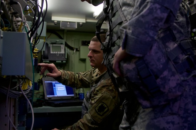 51st ESB Soldiers work on a connection in a communications shelter at Bisbee-Douglas Airport in Bisbee, Ariz. Dec. 8, 2016.